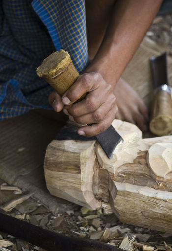 Low section of man carving wood in workshop