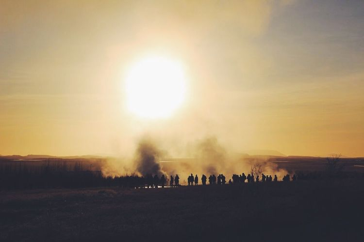 Silhouette People Standing By Steam Emitting From Geyser Against Bright Sky