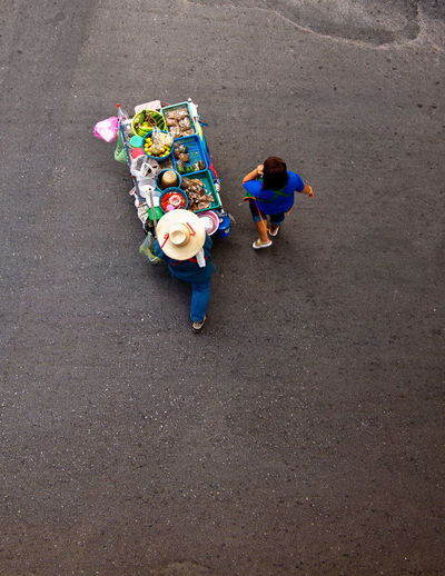High angle view of food vendor and woman walking on road