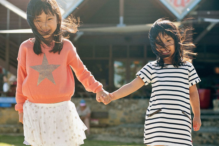 Portrait of smiling sisters holding hands against house