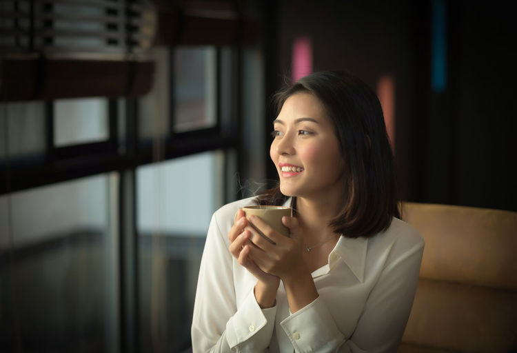 Portrait of a young woman drinking coffee