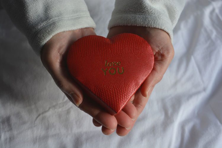 Love you. red heart shaped gift box in hands