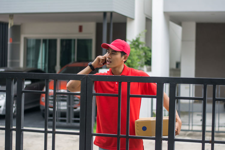 Delivery man standing at closed gate against buildings