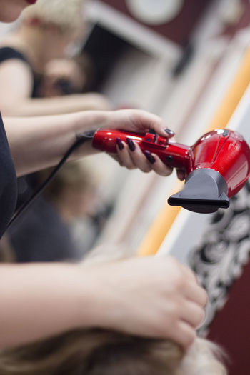 Cropped hand of woman holding hair dryer at home