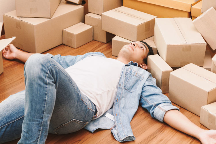 Man working overload and sleep near cardboard boxes around Box Box - Container Cardboard Cardboard Box Casual Clothing Container Indoors  Jeans Lifestyles Lying Down Men Moving House Packing People Real People Relaxation Sitting Three Quarter Length Togetherness Two People Young Adult Young Men