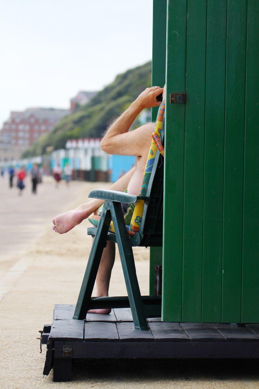 Shirtless Man Sitting On Chair By Beach Hut