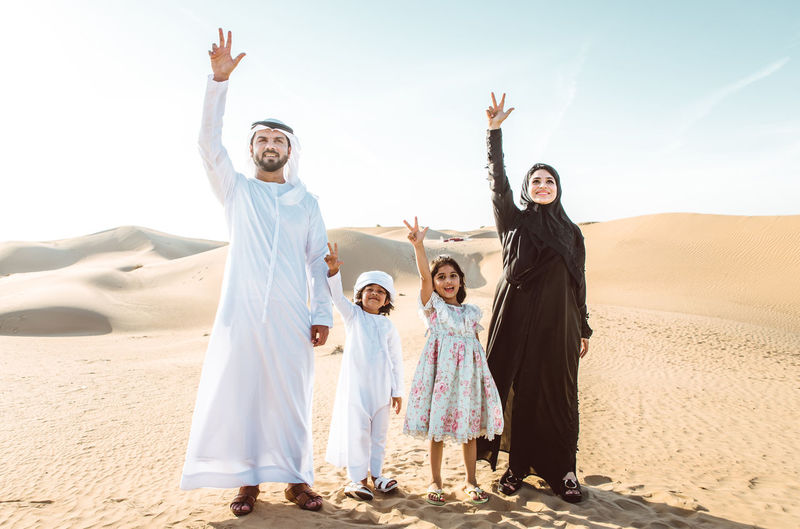 Happy family showing peace sign while standing on sand dune