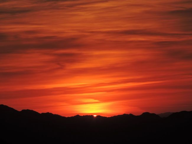 Sun dropping behind mountains Beauty In Nature Scenics Sunset Nature Dramatic Sky Red Tranquility Cloud - Sky Sky Silhouette No People Tranquil Scene Outdoors Astronomy Mountain Star - Space