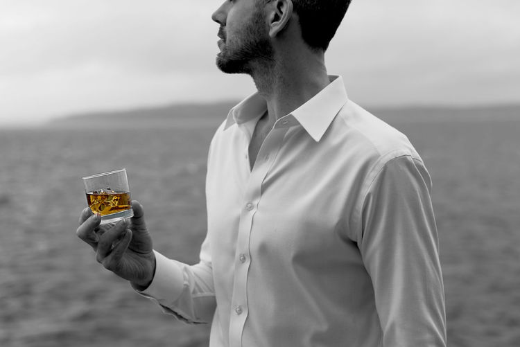 Midsection of man holding whisky in glass while standing on shore