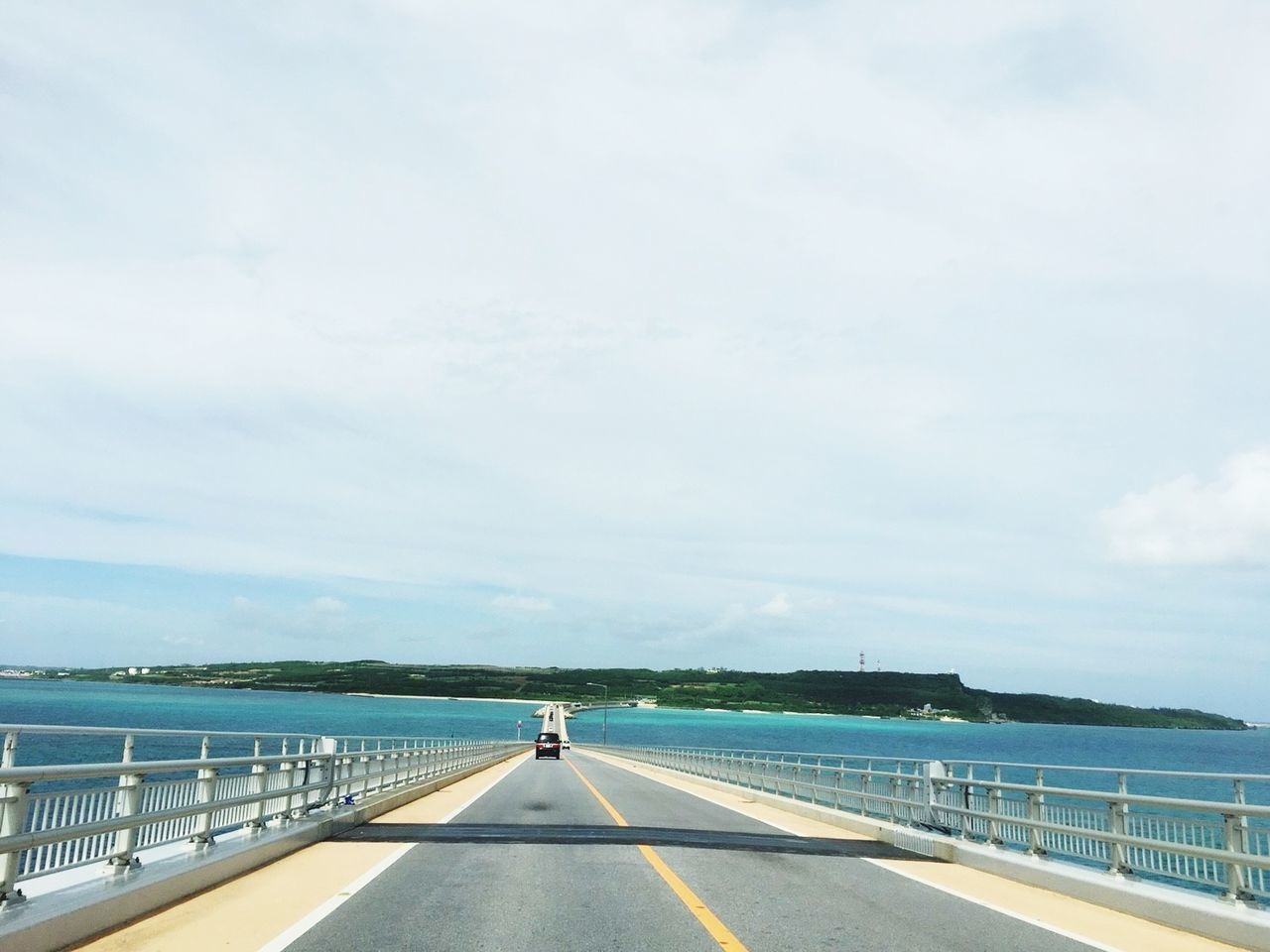 road, transportation, road marking, sky, the way forward, cloud - sky, railing, highway, day, sea, outdoors, scenics, water, no people, nature, beauty in nature