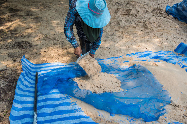 Person cleaning sand at beach