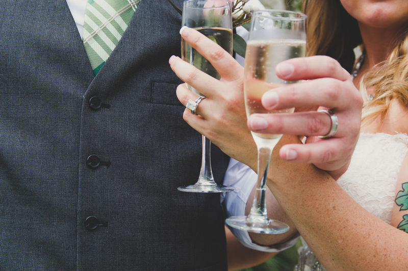 Midsection of newlywed couple holding champagne flutes at wedding ceremony
