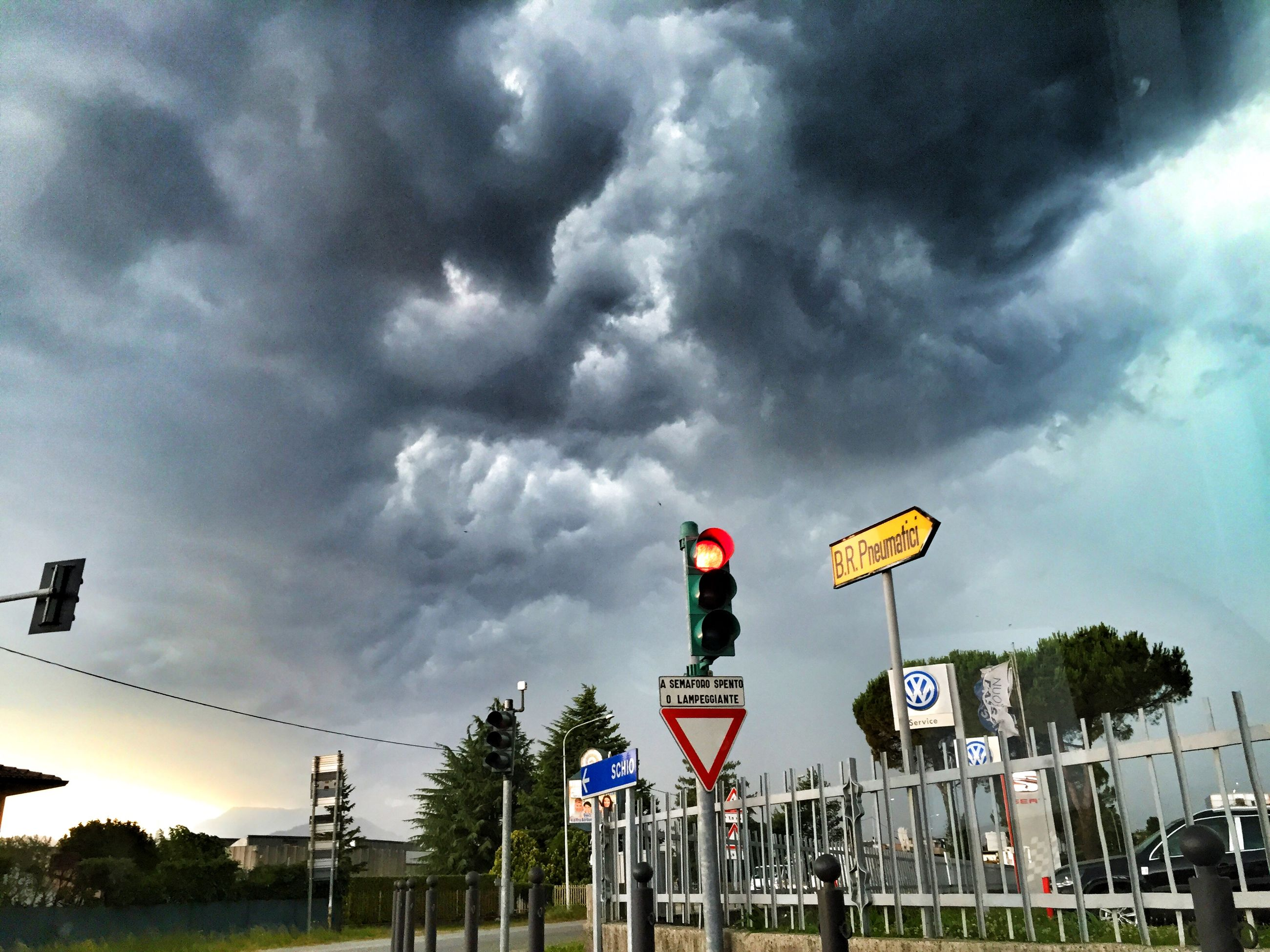 sky, cloud - sky, cloudy, cloud, weather, overcast, built structure, building exterior, low angle view, architecture, road sign, men, transportation, lifestyles, storm cloud, day, full length, outdoors