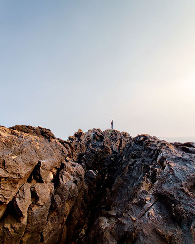 Man standing on rock formation against clear sky