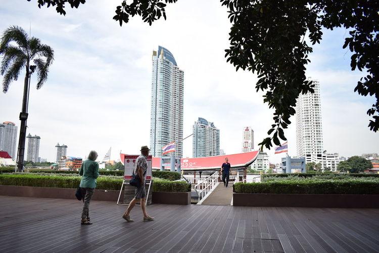 People walking by modern buildings in city against sky