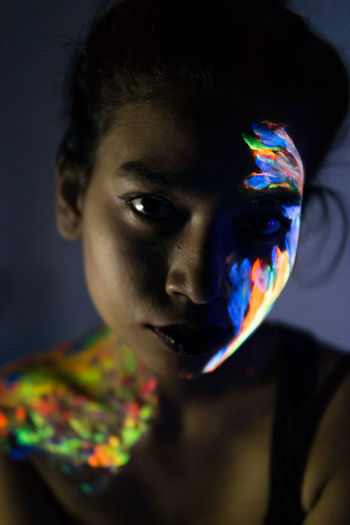 Close-up of woman with glowing paint on face