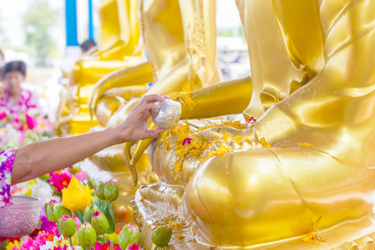 Close-up of woman putting oil on buddha statue at temple