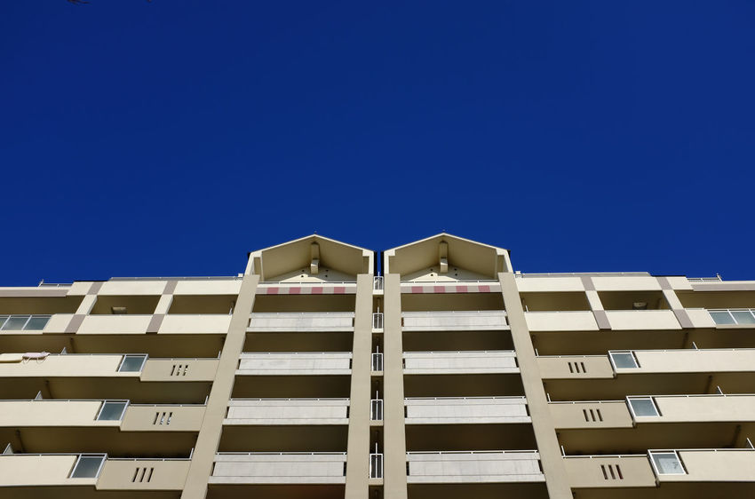 A bland facade to a tall apartment building, with its repetitive architecture, sits in bold contrast against a bright blue sky. Architecture Blue Building Exterior Clear Sky Day Low Angle View No People Outdoors Sky The Week On EyeEm EyeEm Ready