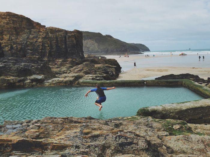 Man jumping in infinity pool against sky