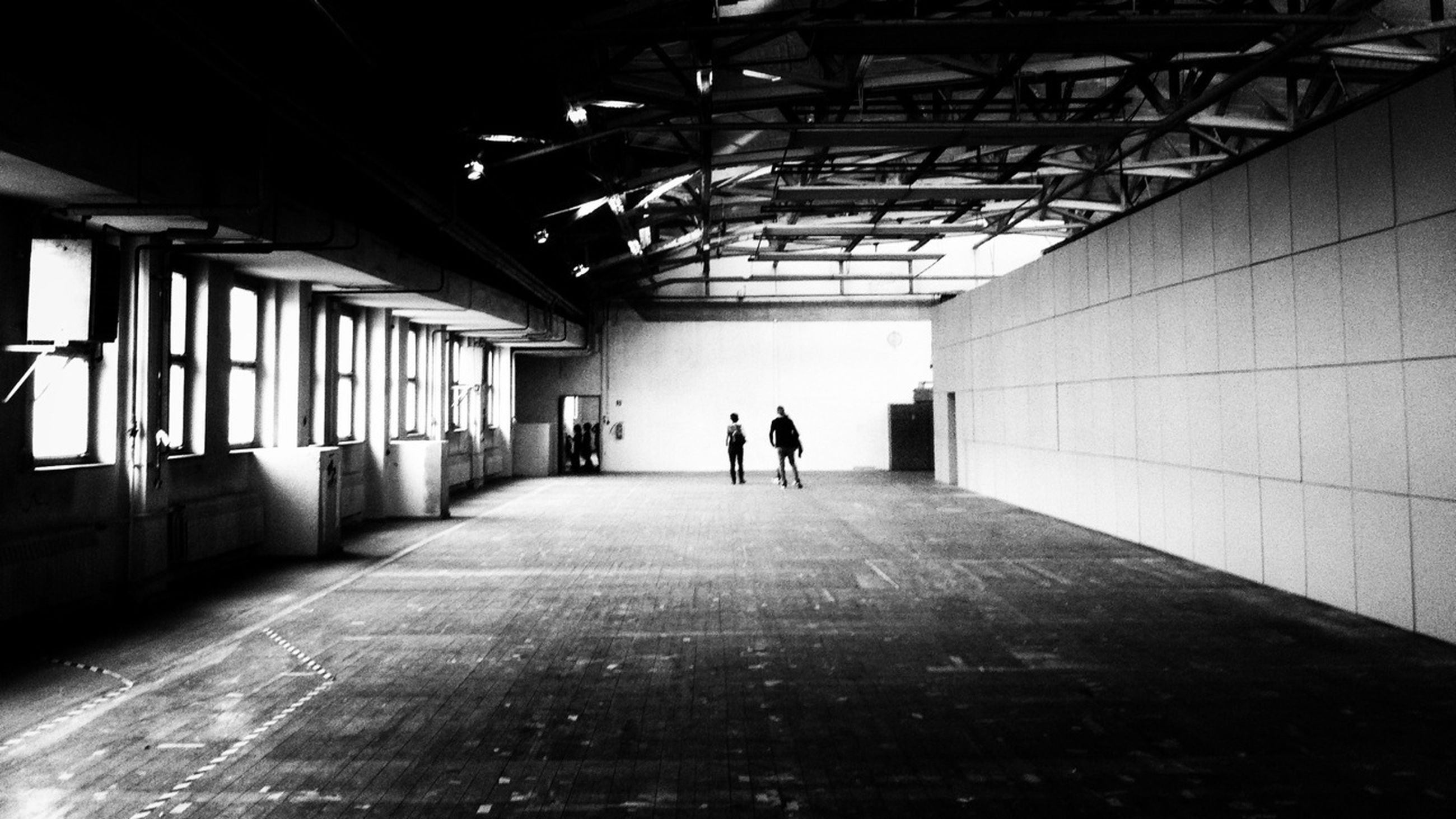 indoors, architecture, built structure, the way forward, corridor, ceiling, men, walking, full length, diminishing perspective, lifestyles, rear view, tunnel, silhouette, flooring, building, unrecognizable person, vanishing point