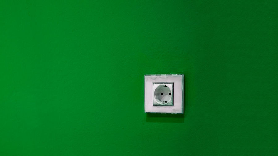 Close-up of electric lamp on green wall