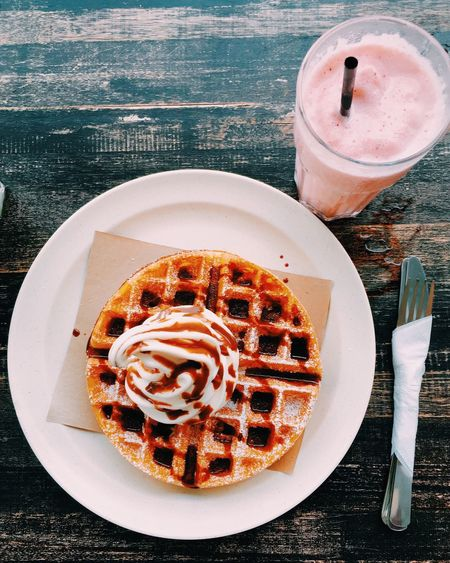 High angle view of fresh ice cream on waffle with chocolate sauce served in plate by smoothie