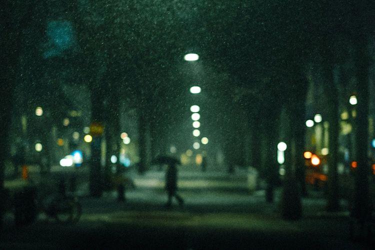 Defocused image of person walking on road at night