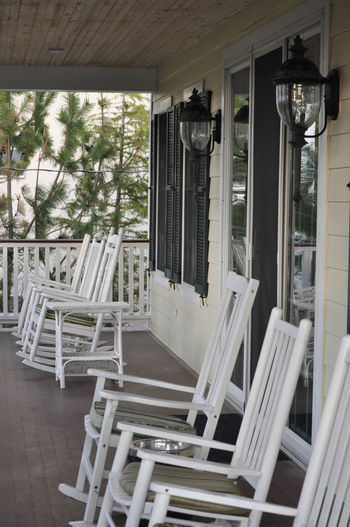 Row of White Rocking Chairs on a Balcony Porch Relaxing Tranquility Architecture Balcony Chair No People Outdoors Rocking Chairs Spring Summer