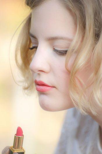 Close-up of woman holding lipstick