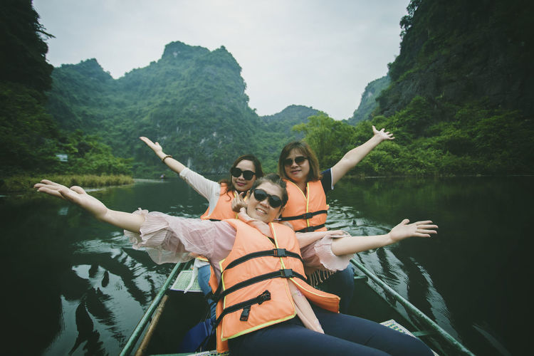 Portrait of smiling women sitting in boat at river