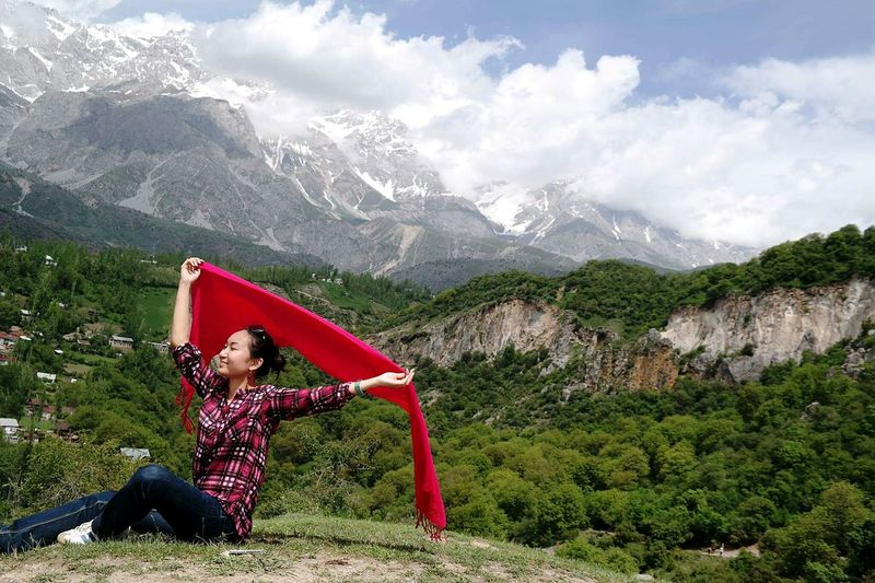 Smiling Woman Holding Red Scarf Against Mountains