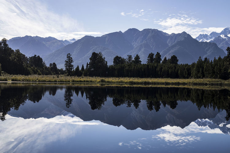 A perfect reflection at Lake Matheson in New Zealand. Lake Matheson Mt Cook WestCoast Beauty In Nature Cloud - Sky Forest Lake Landscape Mountain Mountain Peak Mountain Range Mountains Nature New Zealand Plant Reflection Reflection Lake Scenics - Nature Sky Snow Symmetry Tranquil Scene Tranquility Tree Water
