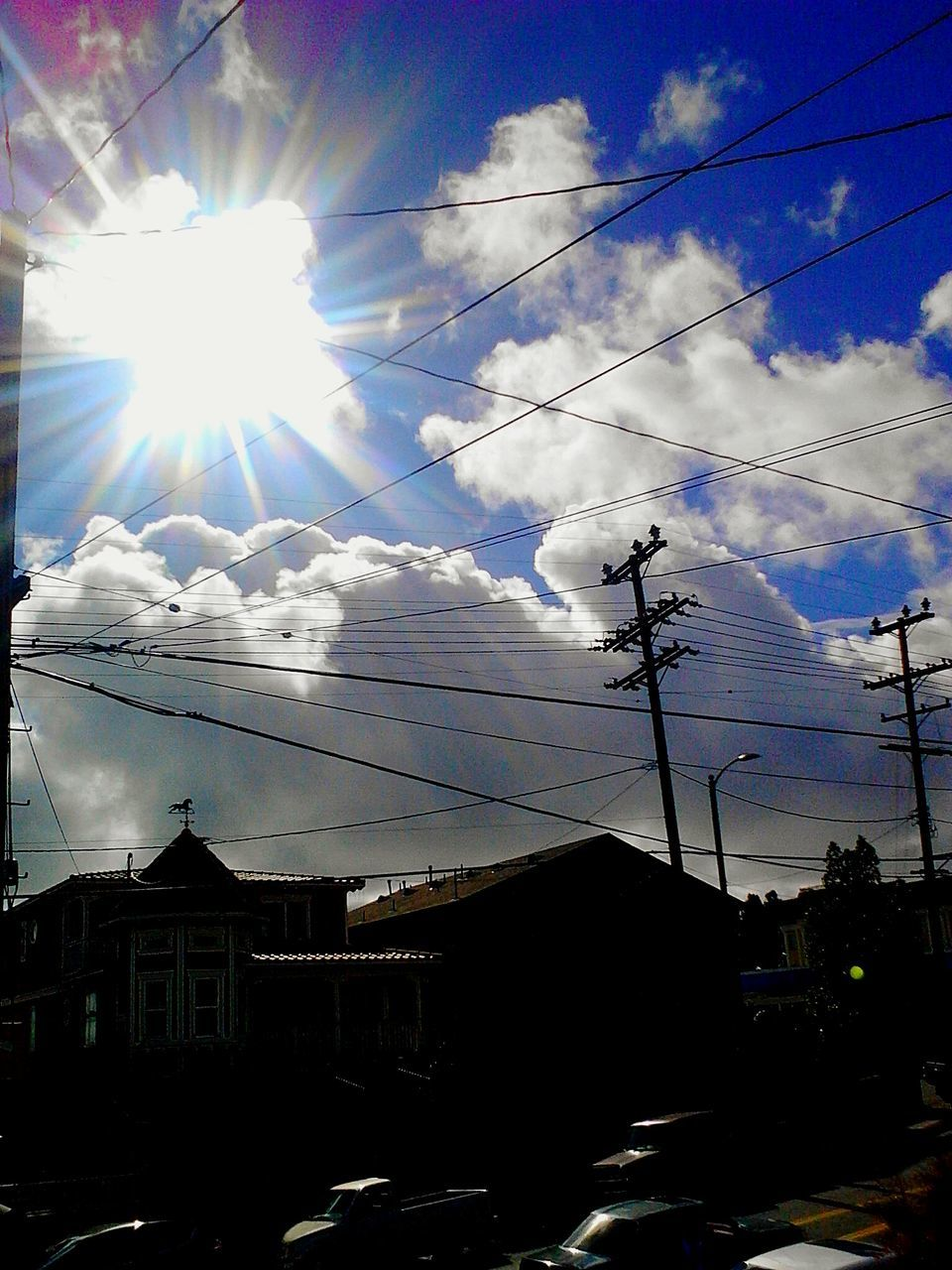cable, sky, sunlight, sunbeam, cloud - sky, power line, power supply, connection, building exterior, no people, built structure, sun, architecture, electricity, low angle view, outdoors, day, electricity pylon, silhouette, nature, technology, telephone line