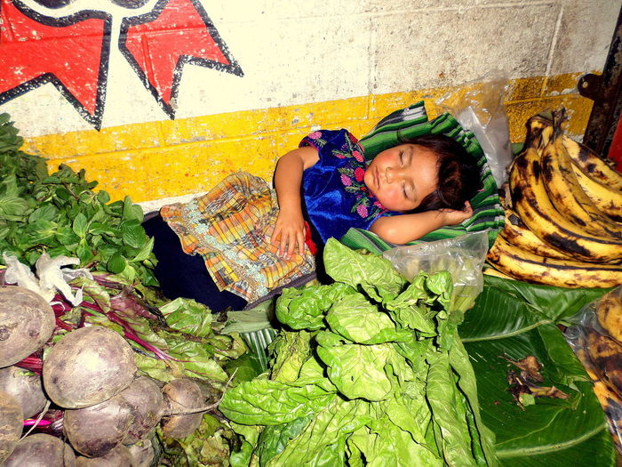 High angle view of girl sleeping by vegetables and fruits at market
