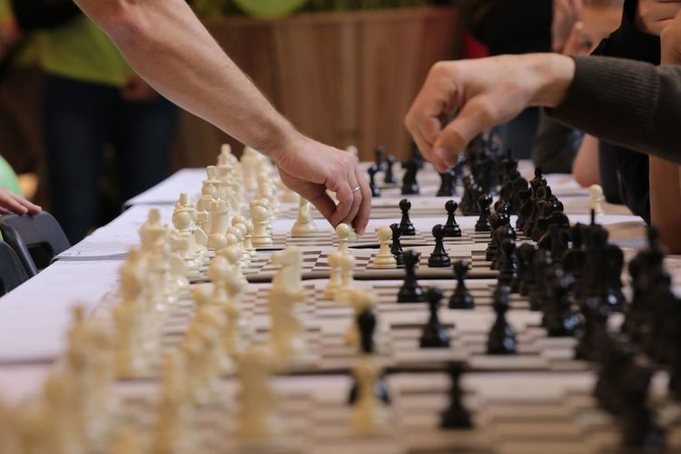 Cropped Image Of Friends Playing Chess