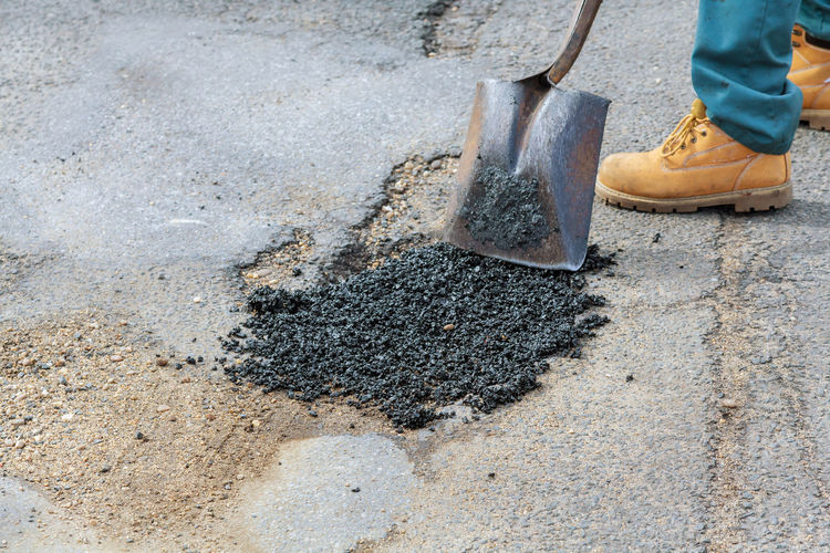 Low section of worker repairing road