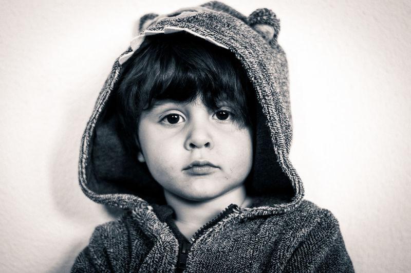 Portrait of cute boy wearing hooded shirt against wall