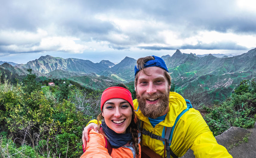 Portrait of happy friends against mountains