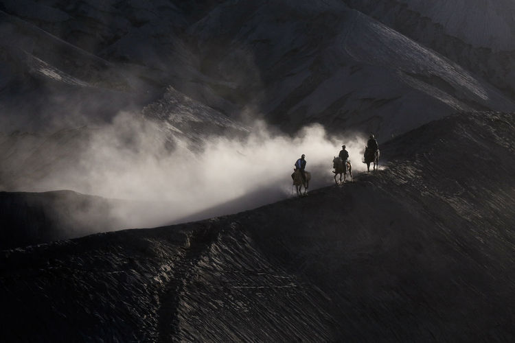 People on mountain against clouds