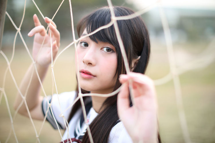 Portrait of young woman standing by sports net
