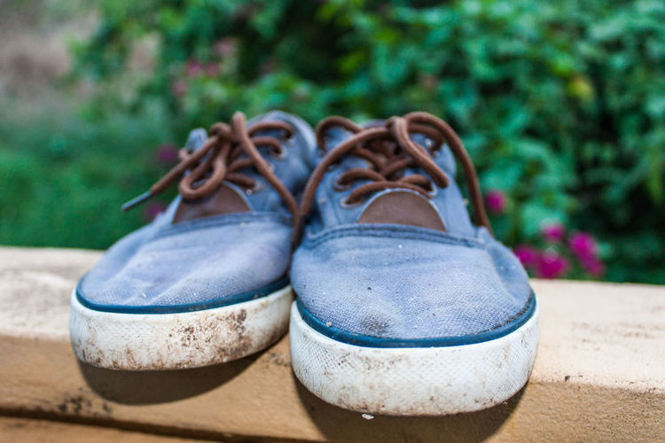 Close-up of canvas shoes on retaining wall