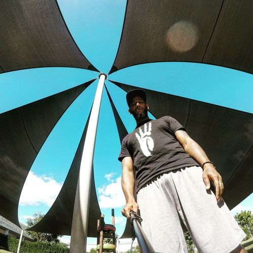 Low angle portrait of man holding monopod under sunshade