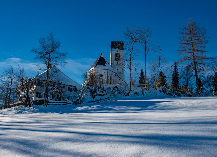Snow covered houses by trees against blue sky