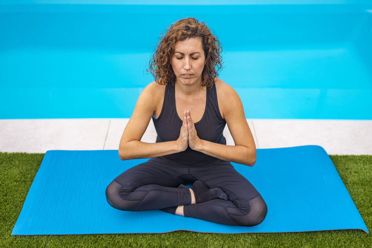Full length of woman meditating while sitting by swimming pool