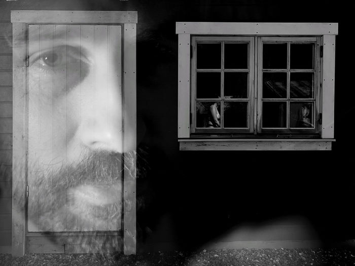 Portrait of man looking through glass window of building