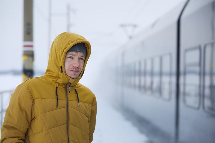Portrait of young man standing against yellow during winter