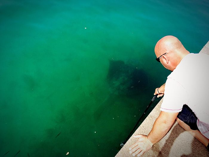 High angle view of mature man fishing in sea while kneeling on retaining wall