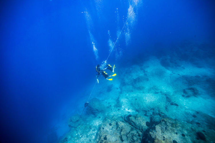 High Angle View Of Scuba Divers Holding Rope Over Rock While Swimming Undersea