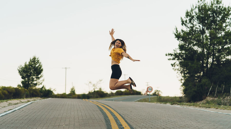 Young woman jumping on road against clear sky