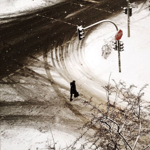 Overhead view of a silhouette person walking on snow covered road